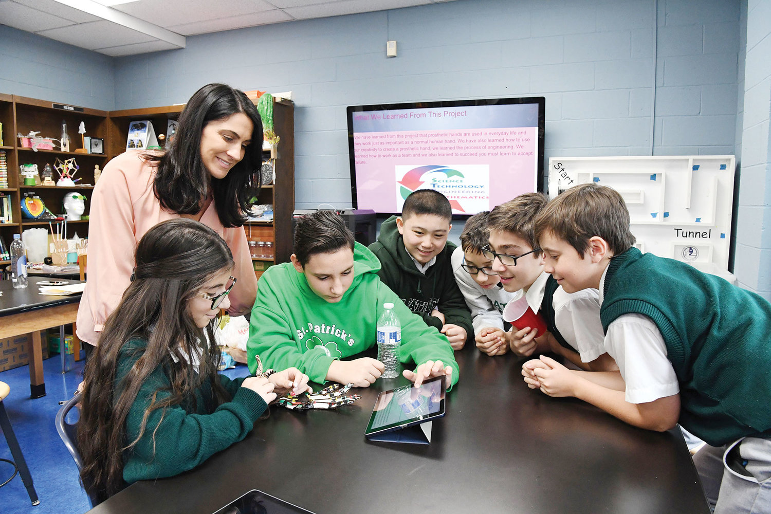 STEM Lab teacher Danielle Tornabene looks on as seventh-graders observe a prosthetic hand created by three of the students. At the table are, from left, Giuliana Westgate, Philip Raneri, Keoni Jensen, Nicholas Borruso, Joseph Lattaruli and Gabriel Walon.