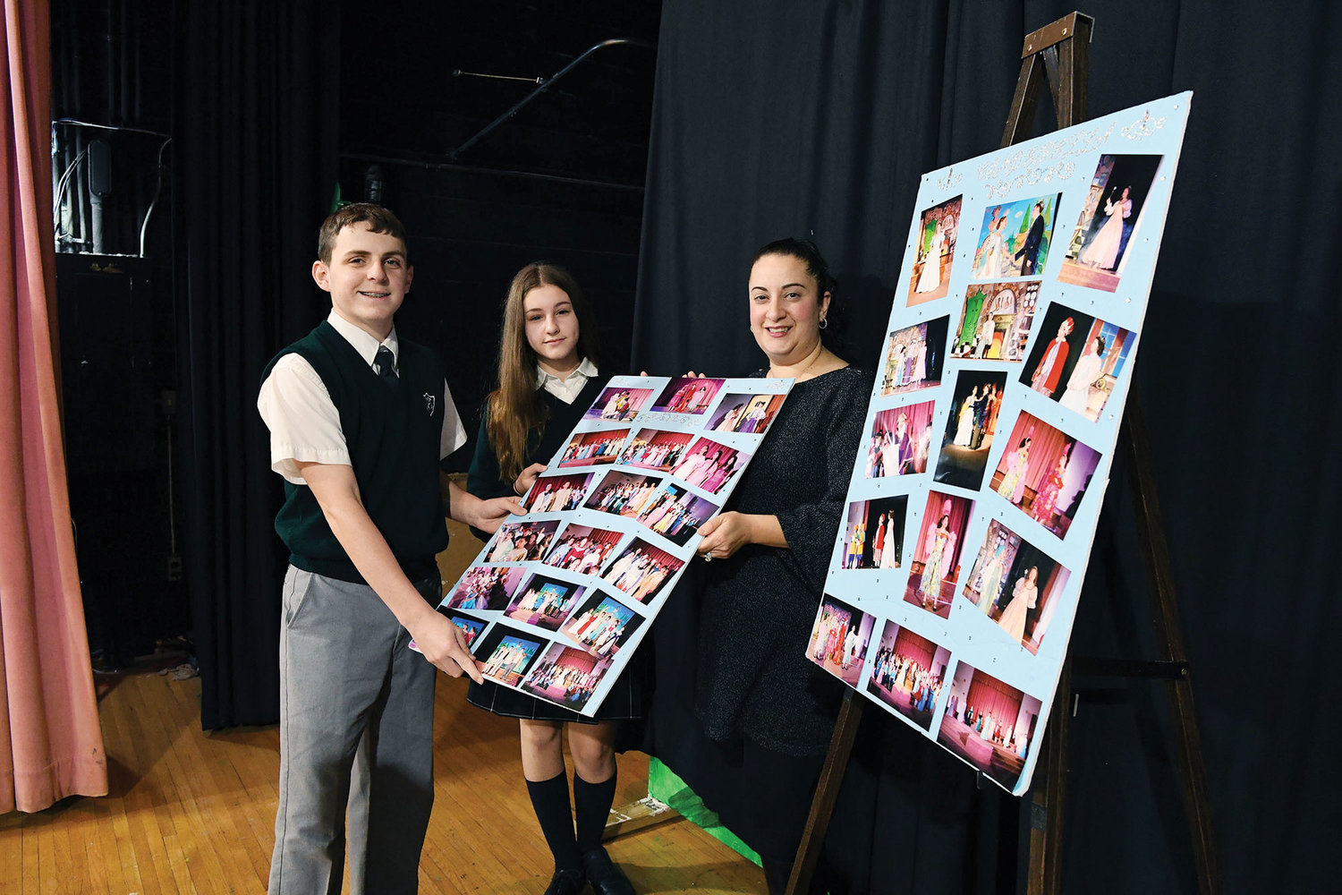 "eighth-graders Timothy Gannon and Sofia Borgognone, and theater arts director Nicole Grasso, hold photos of the school's November production of ""Cinderella"" on stage in the auditorium."