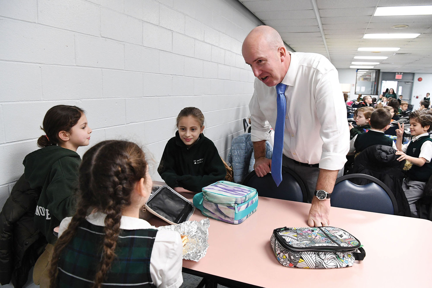 Sadowski talks with fourth-grade students in the cafeteria; the students are Misty Spano, with braids, Gabriella Borgognone and Alexis Testaverde.
