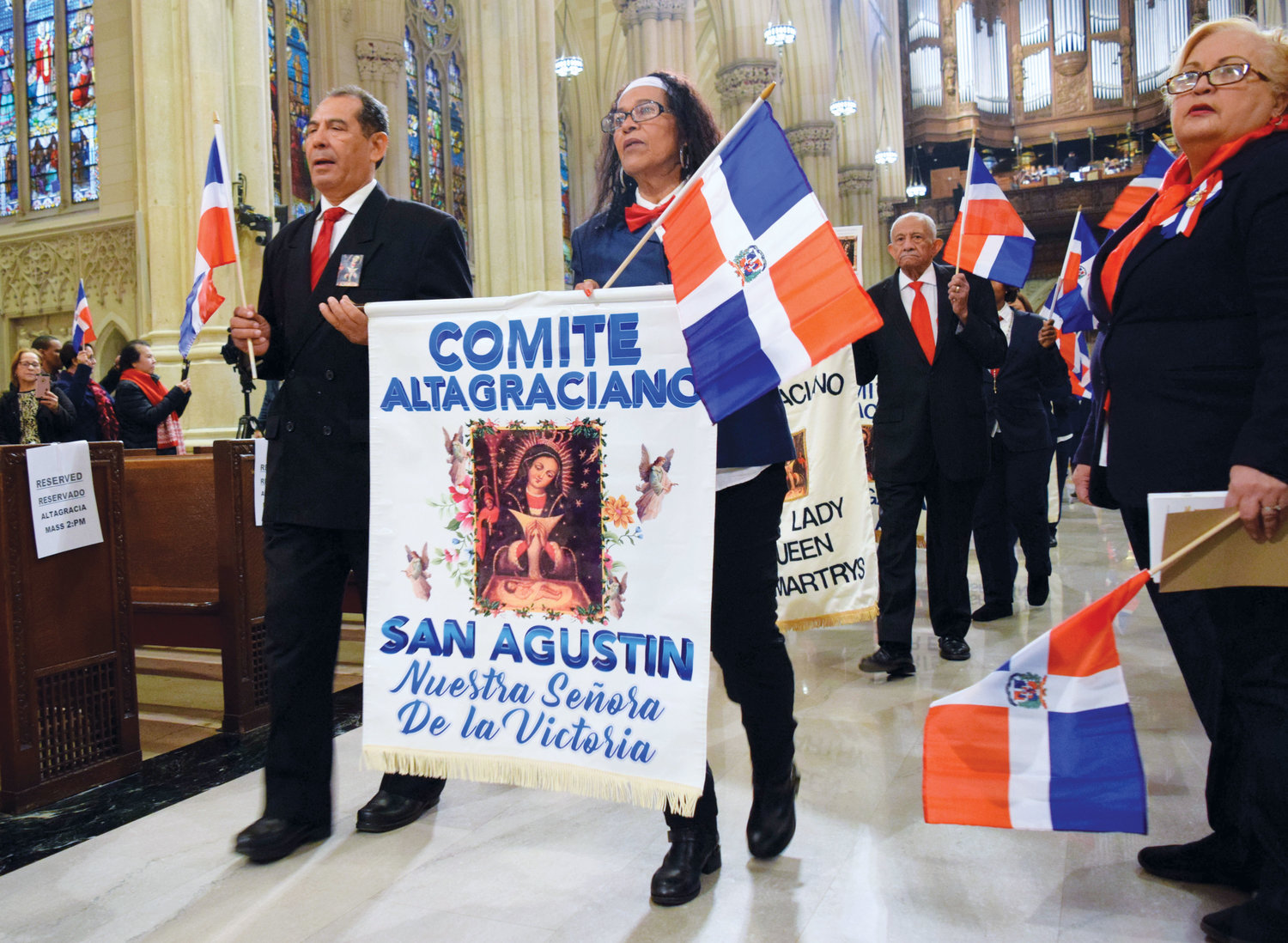The banner of St. Augustine-Our Lady of Victory parish in the Bronx is held by members of the Our Lady of Altagracia Committee during the Jan. 13 Mass honoring the protectress of the Dominican Republic. More than 1,200 people attended the Spanish Mass in St. Patrick's Cathedral.