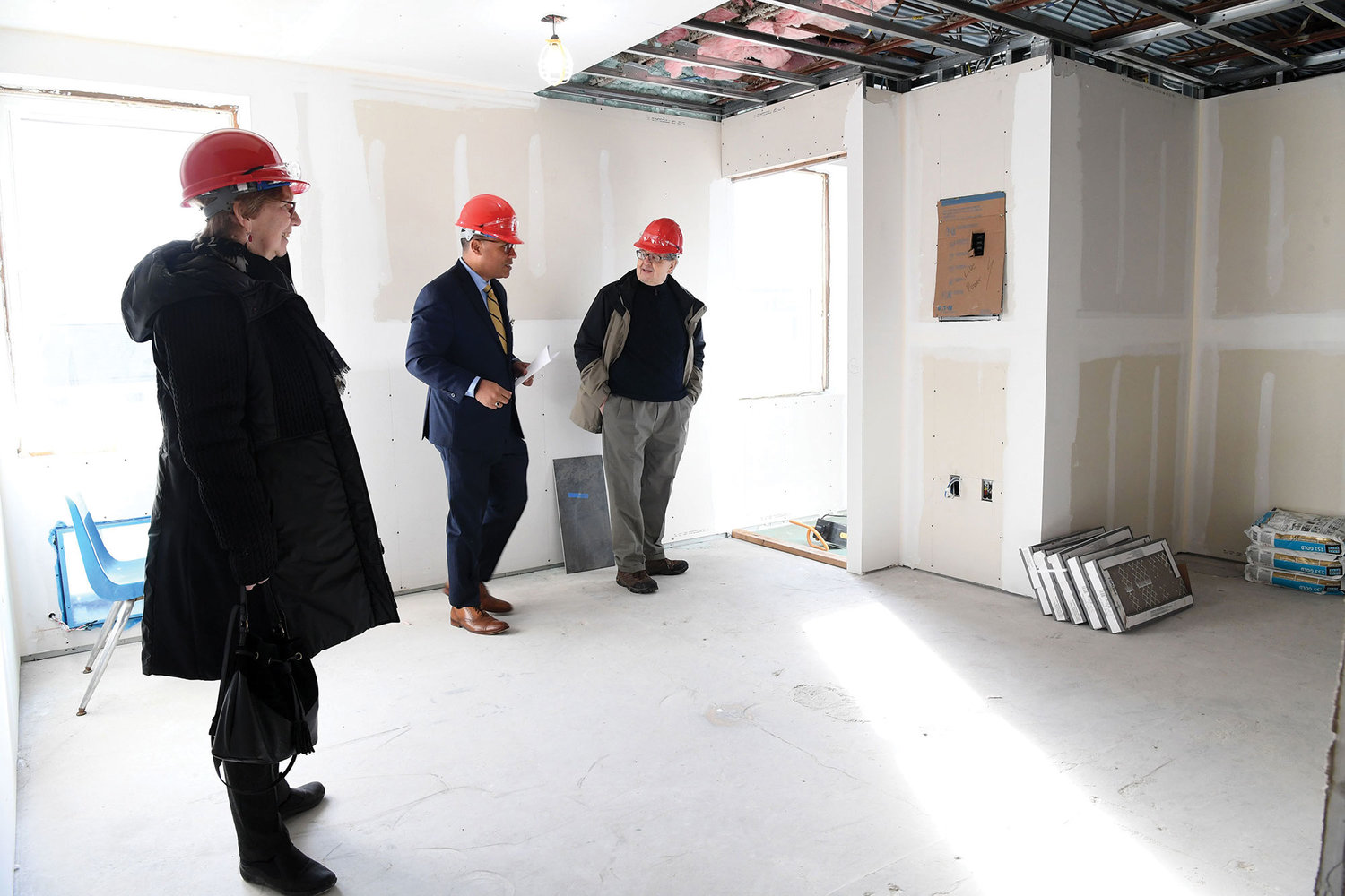 Hugo Pizarro, a senior vice president and chief experience officer for ArchCare, center, shows Pat and Thomas Alberto the construction progress on ArchCare's $3 million project to provide independent housing for young adults with autism at St. Teresa parish on Staten Island Jan. 17.