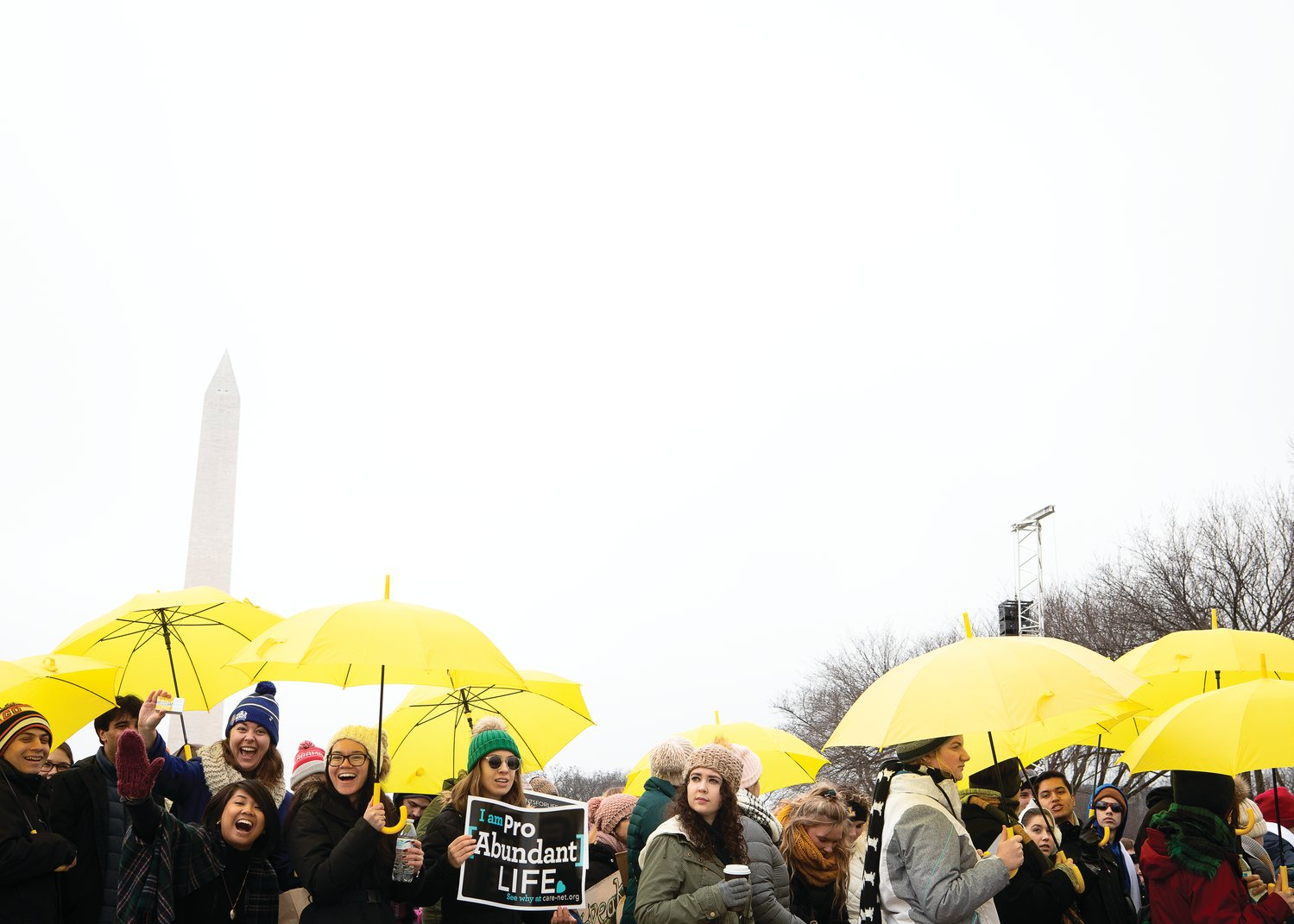 Participants march under rainy skies with the Washington Monument in the background.