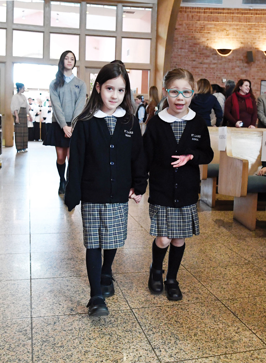 Emily Sciusco and Ella Ficchi, kindergarteners at St. Clare School, walk together in the procession at the start of Mass Jan. 27 at Holy Rosary Church to celebrate the start of National Catholic School Week on Staten Island.