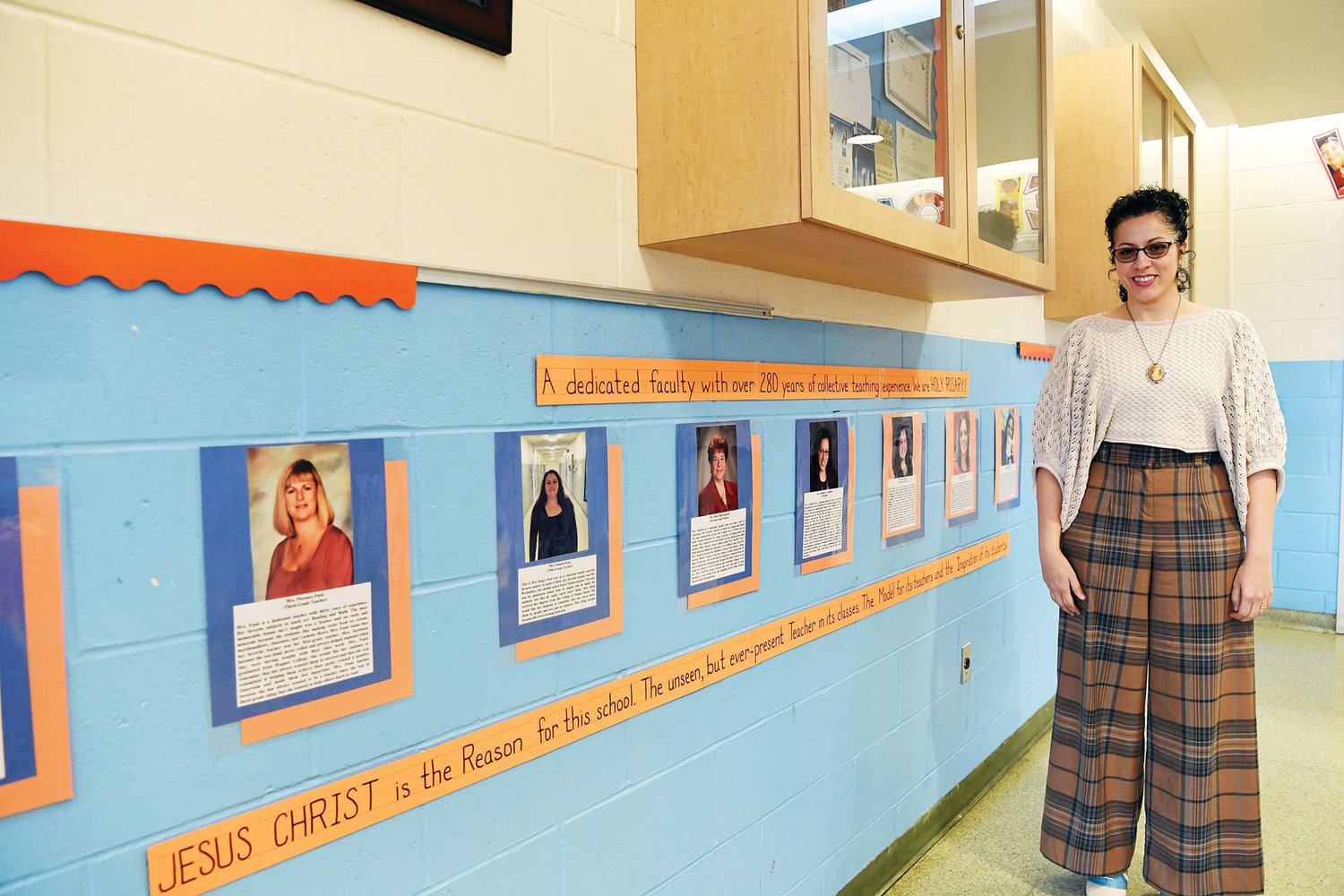 Elizabeth Campbell, principal of Holy Rosary School, shows the Teachers Wall of Fame in the school lobby.