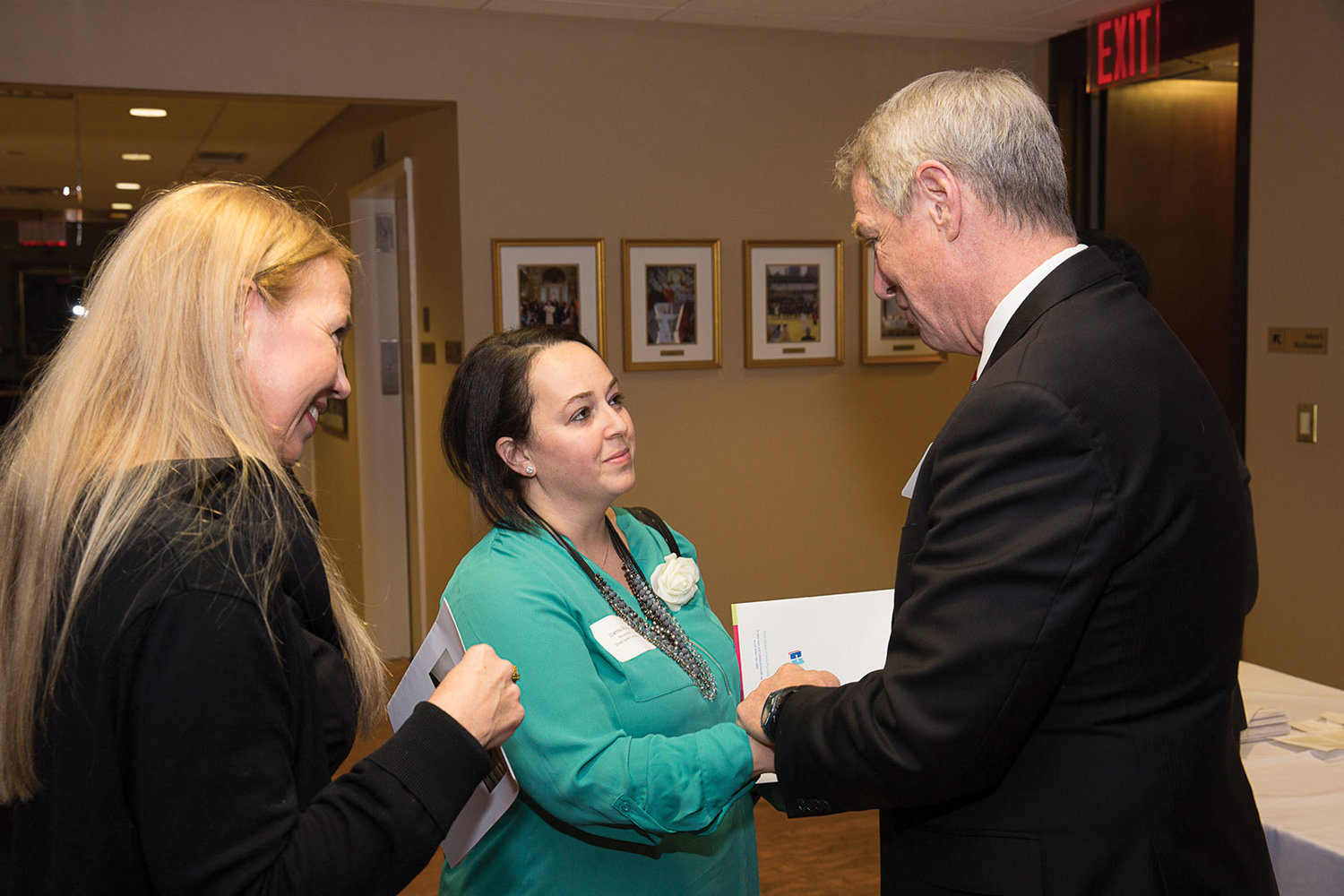 Dr. Timothy McNiff, superintendent of schools, greets Curran Fellowship candidate Joanna Moore, center, of Resurrection School in Rye, and GinaMarie Fonte, principal of Resurrection School.