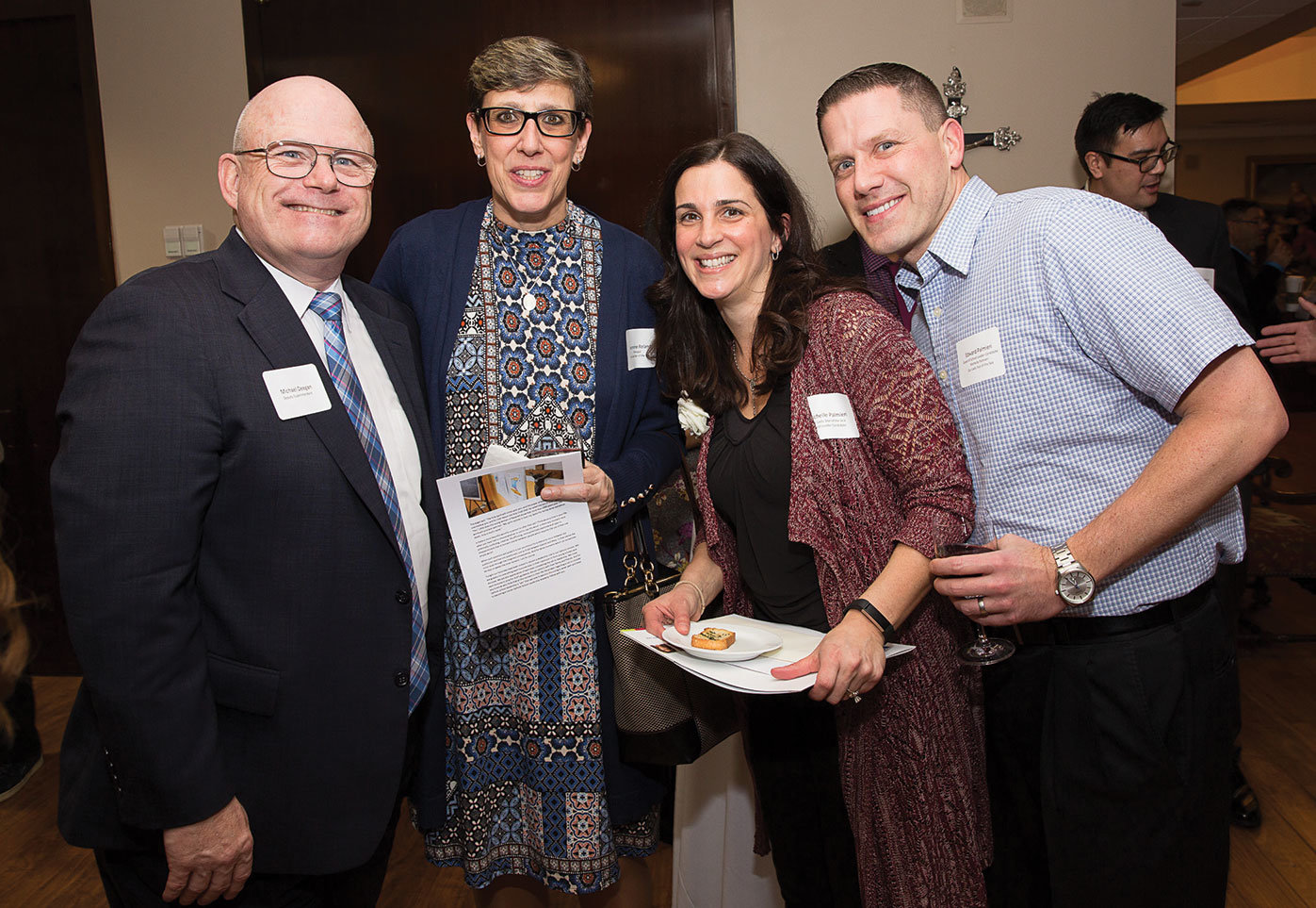 Michael Deegan, far left, deputy superintendent of schools in the archdiocese, joins Jeannine Roland, principal of Our Lady Star of the Sea, Staten Island; Michelle Palmieri, teacher at Our Lady Star of the Sea; and Edward Palmieri, Ms. Palmieri's husband, at the Evening of Teacher Recognition and Call to Discernment at the New York Catholic Center in Manhattan Jan. 24. Ms. Palmieri was one of more than 40 distinguished teachers in the archdiocese invited to apply for a Curran Fellowship.