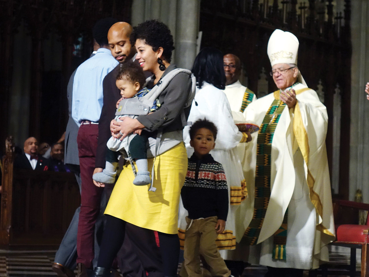 A young family walks closely together after presenting the offertory gifts to Auxiliary Bishop Guy Sansaricq of the Diocese of Brooklyn at the archdiocesan Black History Month Mass in St. Patrick's Cathedral Feb. 3. This year's Black History Month celebration was spread over the entire weekend, incorporating a film screening at the Sheen Center and a day of service.