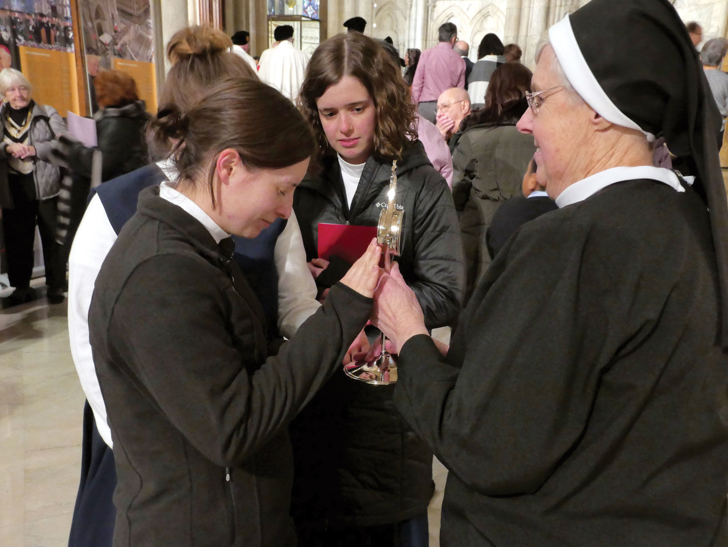 Sister Ritamary Schulz, A.S.C.J., provincial superior for the U.S. Province, holds Blessed Clelia's reliquary before a postulant in prayer.