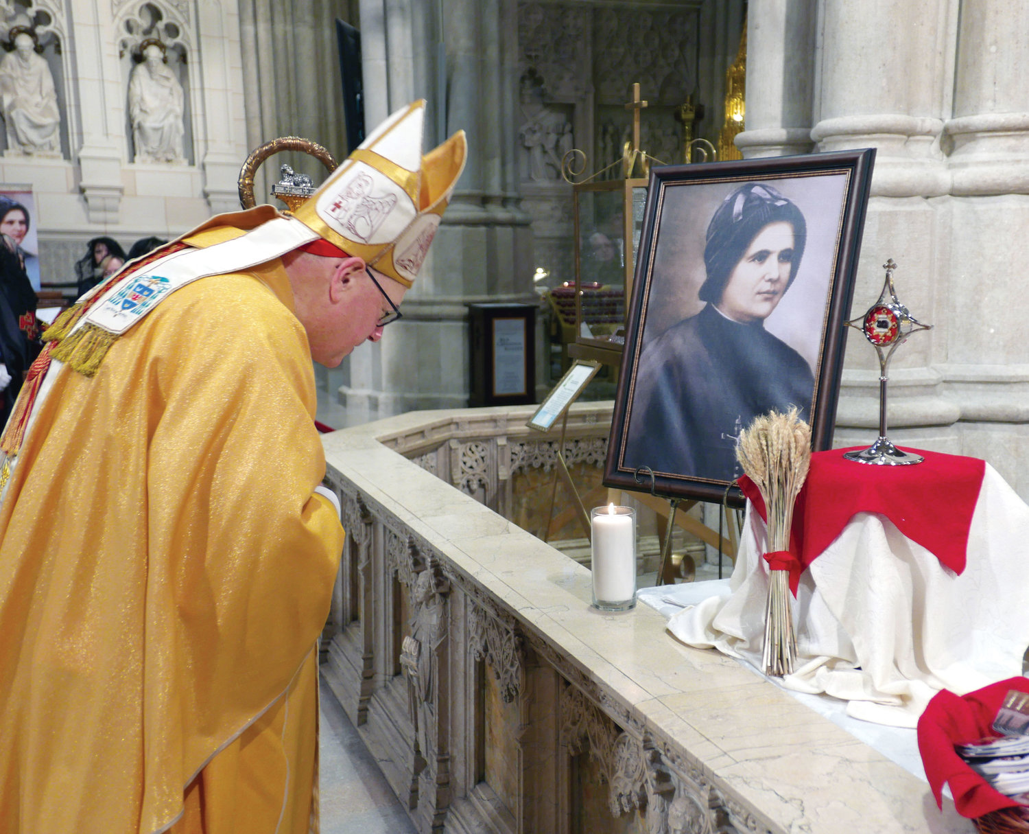 Cardinal Dolan bows before a portrait and the relic of Blessed Clelia Merloni during the opening procession at the Mass of thanksgiving for the beatification of Blessed Clelia at St. Patrick's Cathedral Feb. 9.