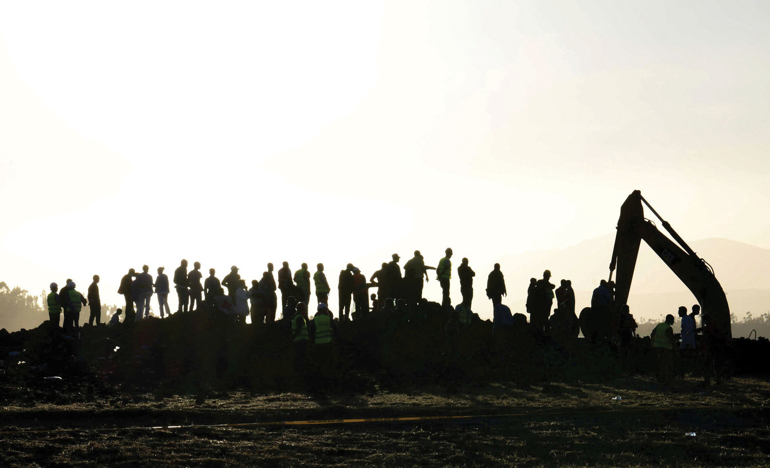 People watch a tractor excavate the Ethiopian Airlines Flight ET 302 plane crash March 10 near Bishoftu, Ethiopia.