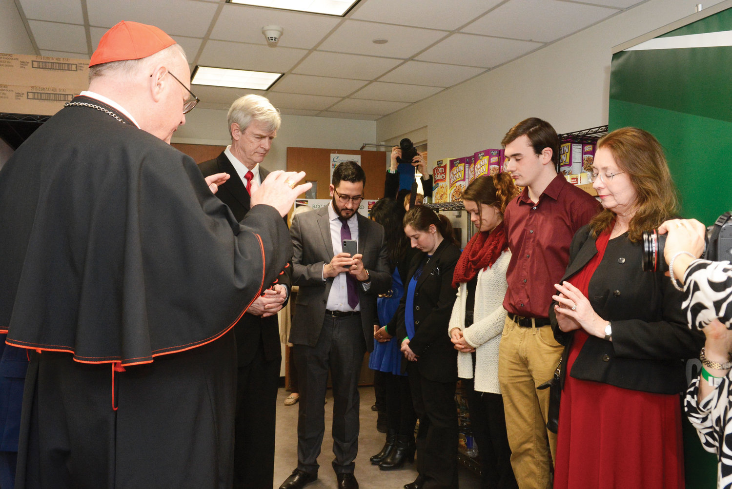 The cardinal leads a prayer during the blessing of the Rockland Community College Food Cupboard.