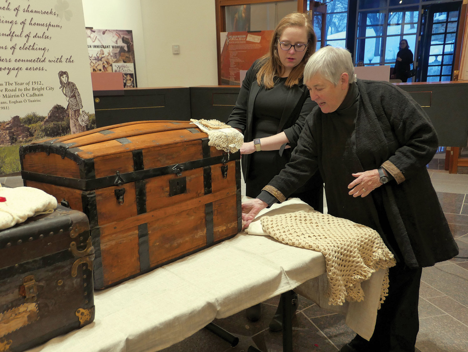 A photo exhibit of the Irish Mission at Watson House opened March 7 in the Archives Building at St. Joseph's Seminary in Dunwoodie. Dr. Maureen Murphy, featured speaker at the exhibit opening touches a trunk used by her paternal grandmother, Martha Thompson, when she emigrated from Ireland in 1900. With Dr. Murphy is Kate Feighery, archdiocesan archivist.