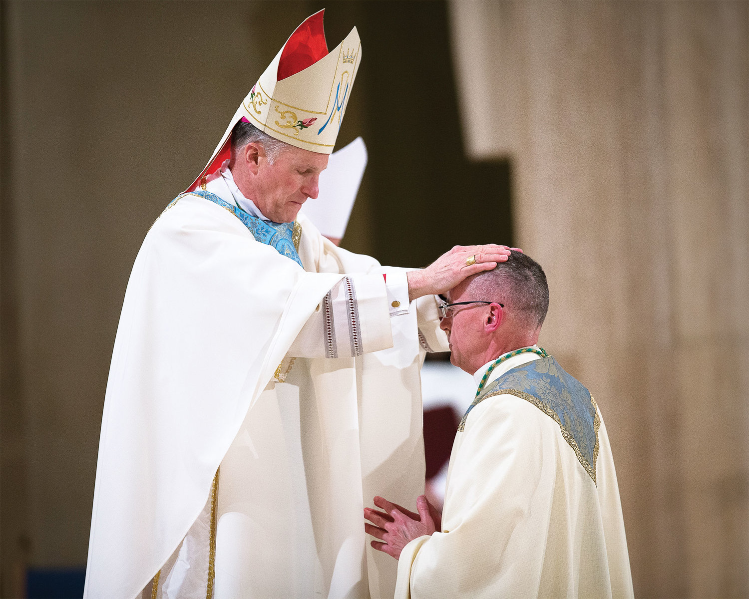 Archbishop Timothy P. Broglio of the U.S. Archdiocese for the Military Services lays his hands upon the head of Auxiliary Bishop William J. Muhm during his episcopal ordination at the Basilica of the National Shrine of the Immaculate Conception in Washington, D.C., March 25.