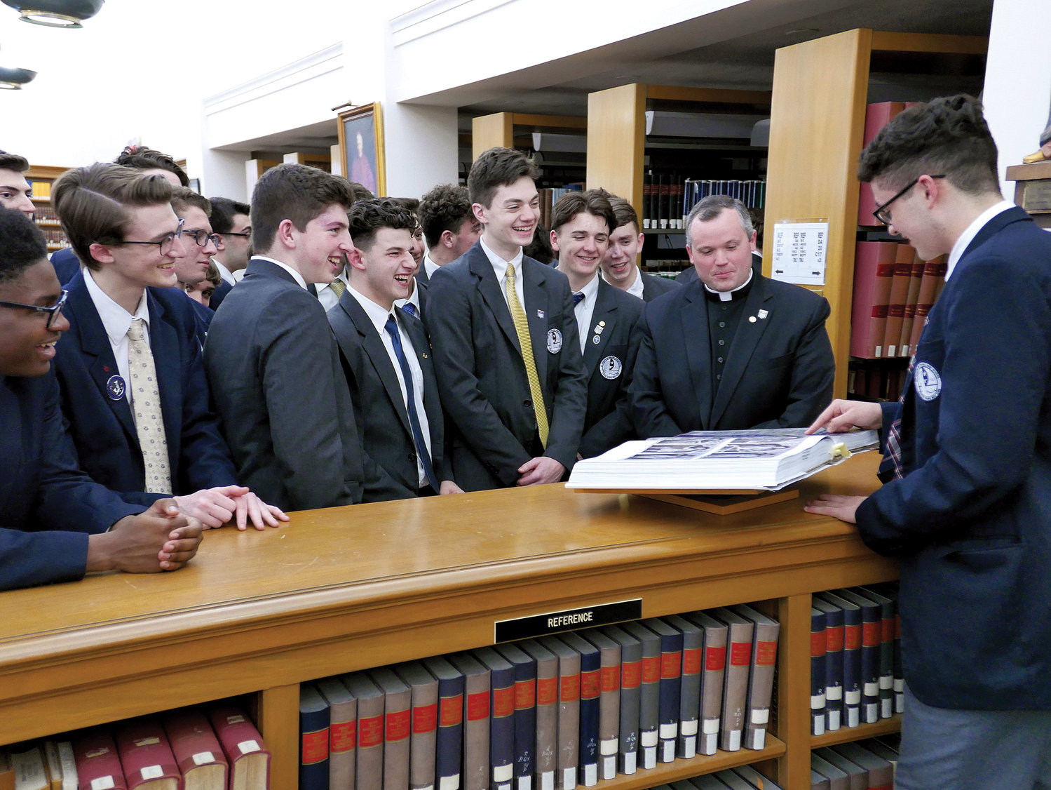 St. Joseph by-the-Sea High School students check out a book with school chaplain Father John McCarthy in the library at St. Joseph's Seminary in Dunwoodie March 21. Students toured the seminary as part of an Evening for Vocations. Forty-seven guests from St. Joseph by-the-Sea attended.