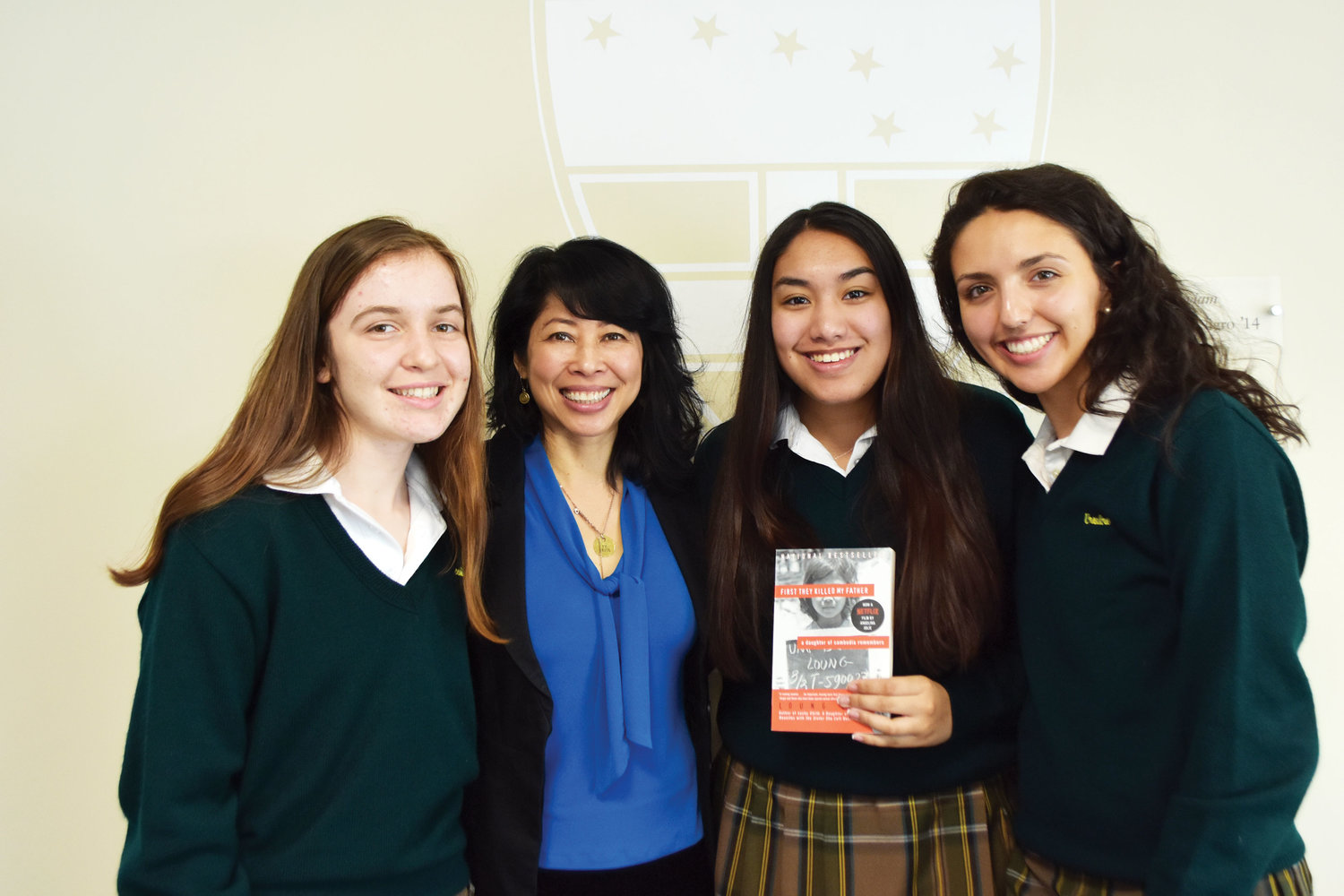 Loung Ung, second from left, meets with Ursuline School seniors Juliet Sullivan, left; Deanna Rahman, holding book; and Natalia Matar, following her inspiring speech at the sixth annual Global Education and Serviam Symposium at the New Rochelle school March 14. The three students are taking the school's global scholars seminar and are the managing editors of the school newspaper, Unison.