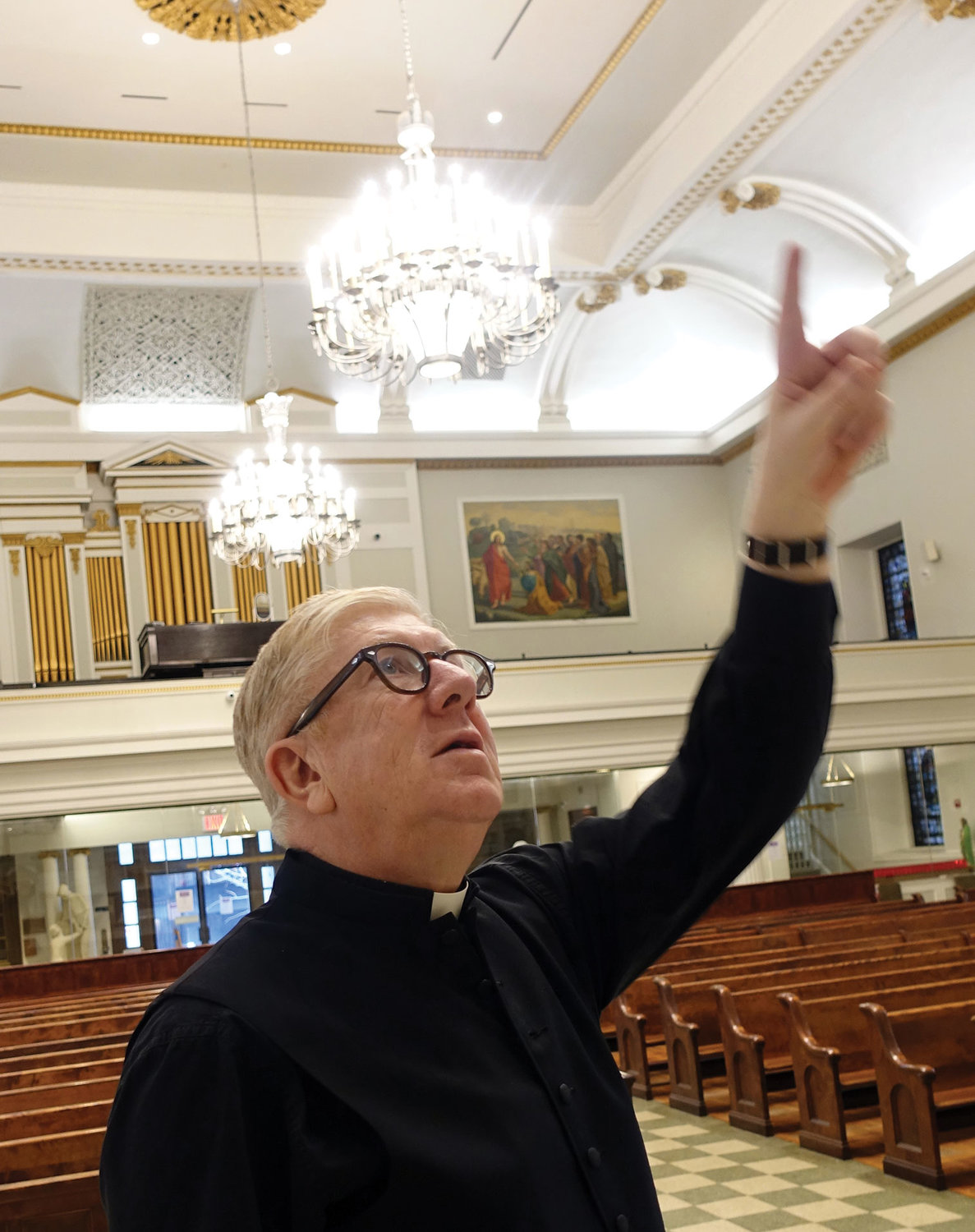Father Jarlath Quinn, the pastor of St. Peter and Our Lady of the Rosary parish, points to a detail in artwork.