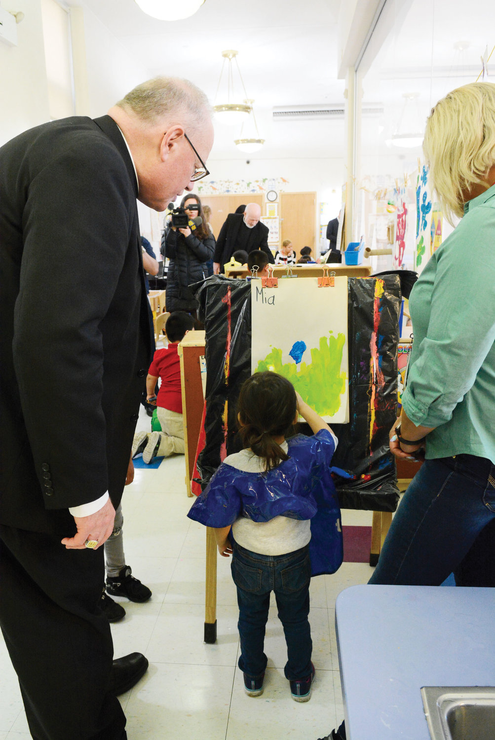 Cardinal Dolan watches a child paint.