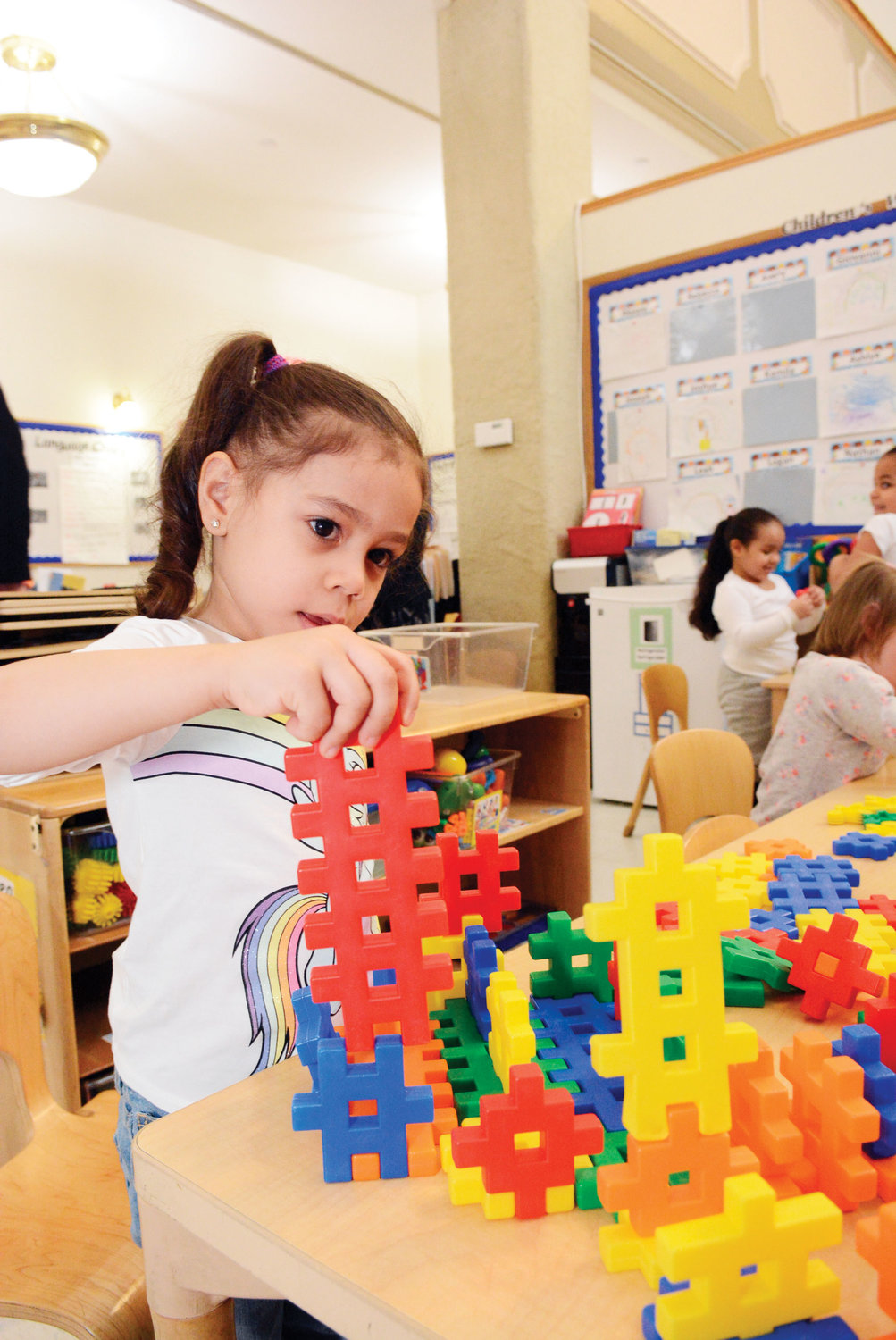 Mya Torres, 3, is using building blocks during Cardinal Dolan's visit March 14 to the Msgr. Patrick J. Boyle Head Start program.