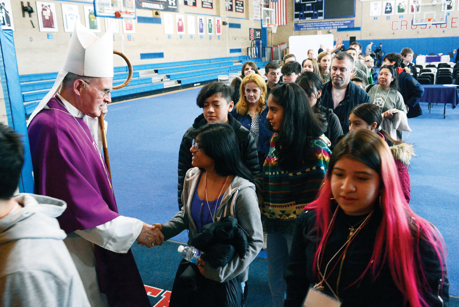 Retired Auxiliary Bishop Gerald Walsh, the principal celebrant, greets students after the closing Mass.