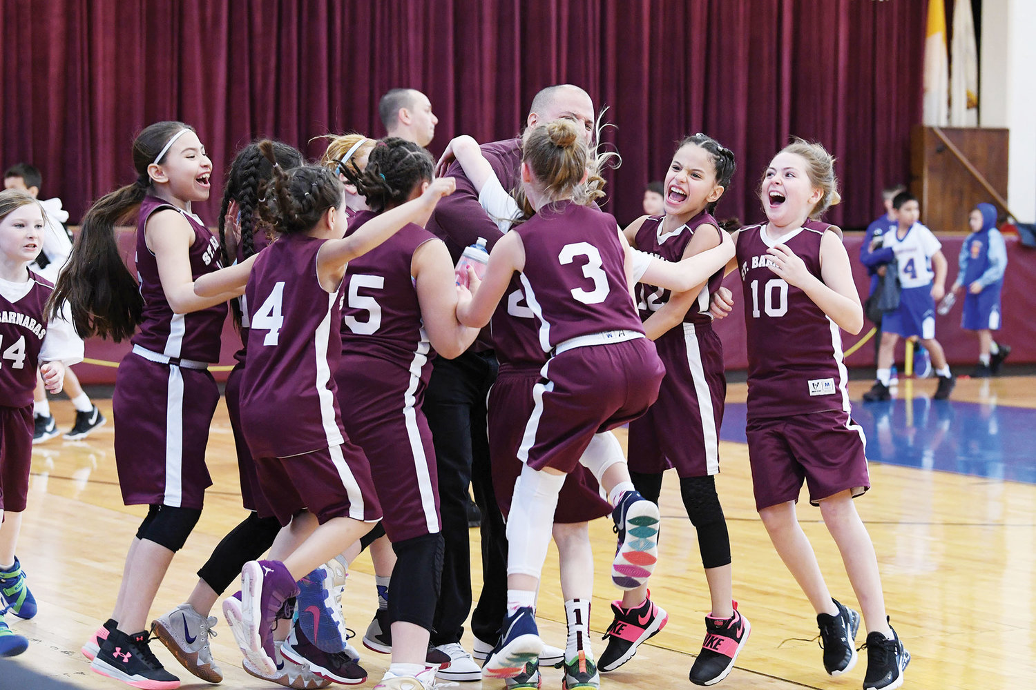 The fourth-grade girls from St. Barnabas, the Bronx, celebrate winning their CYO New York basketball championship with an 18-13 victory over St. Paul, Congers, at Msgr. Farrell High School on Staten Island March 16.