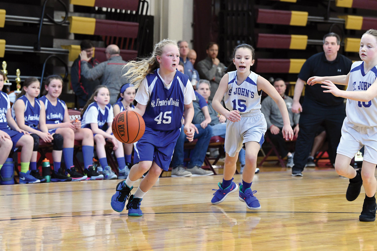 Carley Voce of St. Francis of Assisi, West Nyack, drives to the basket against Gianna Dolan, center, and Ashley Koch, right, of St. John the Evangelist, Mahopac, in the fifth grade girls' championship game.