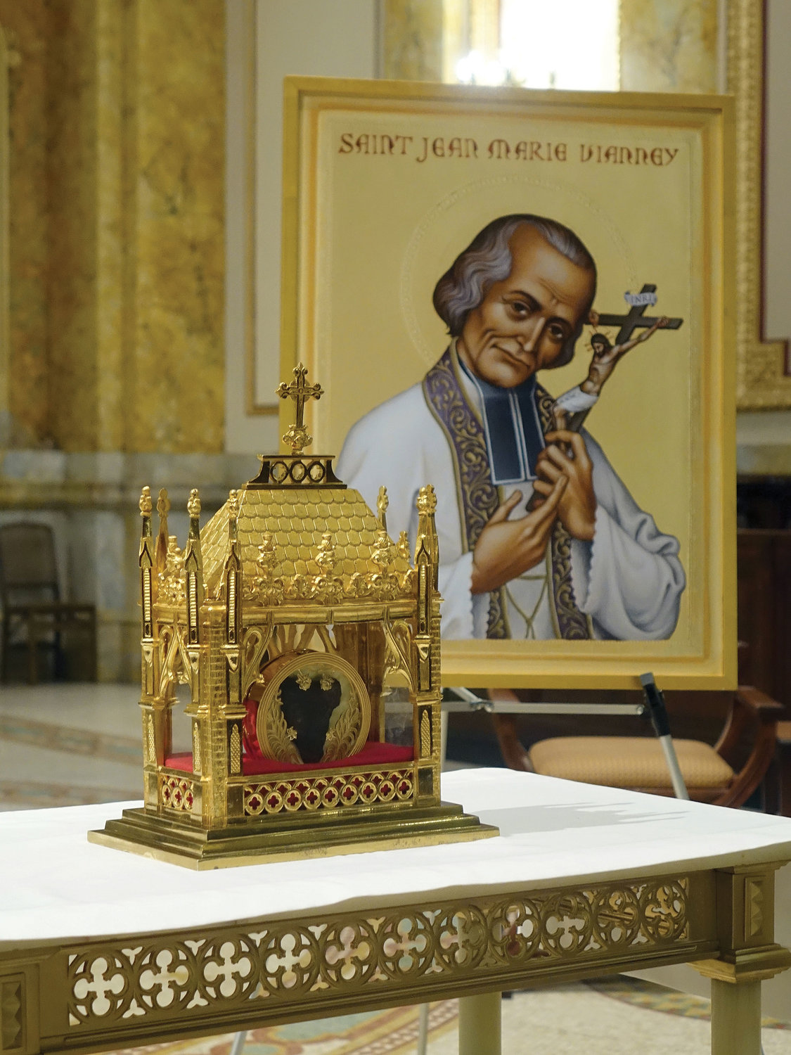 An icon of St. John Vianney, known as the Curé of Ars, left, is displayed near the relic.