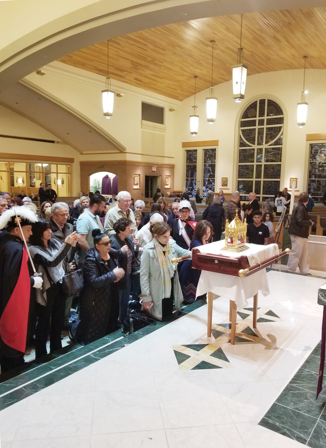 People pray before and venerate the incorrupt heart relic of St. John Vianney during its visit to Our Lady Star of the Sea Church on Staten Island following the 7 p.m. Mass April 7. The relic remained at the church overnight through early morning April 8.