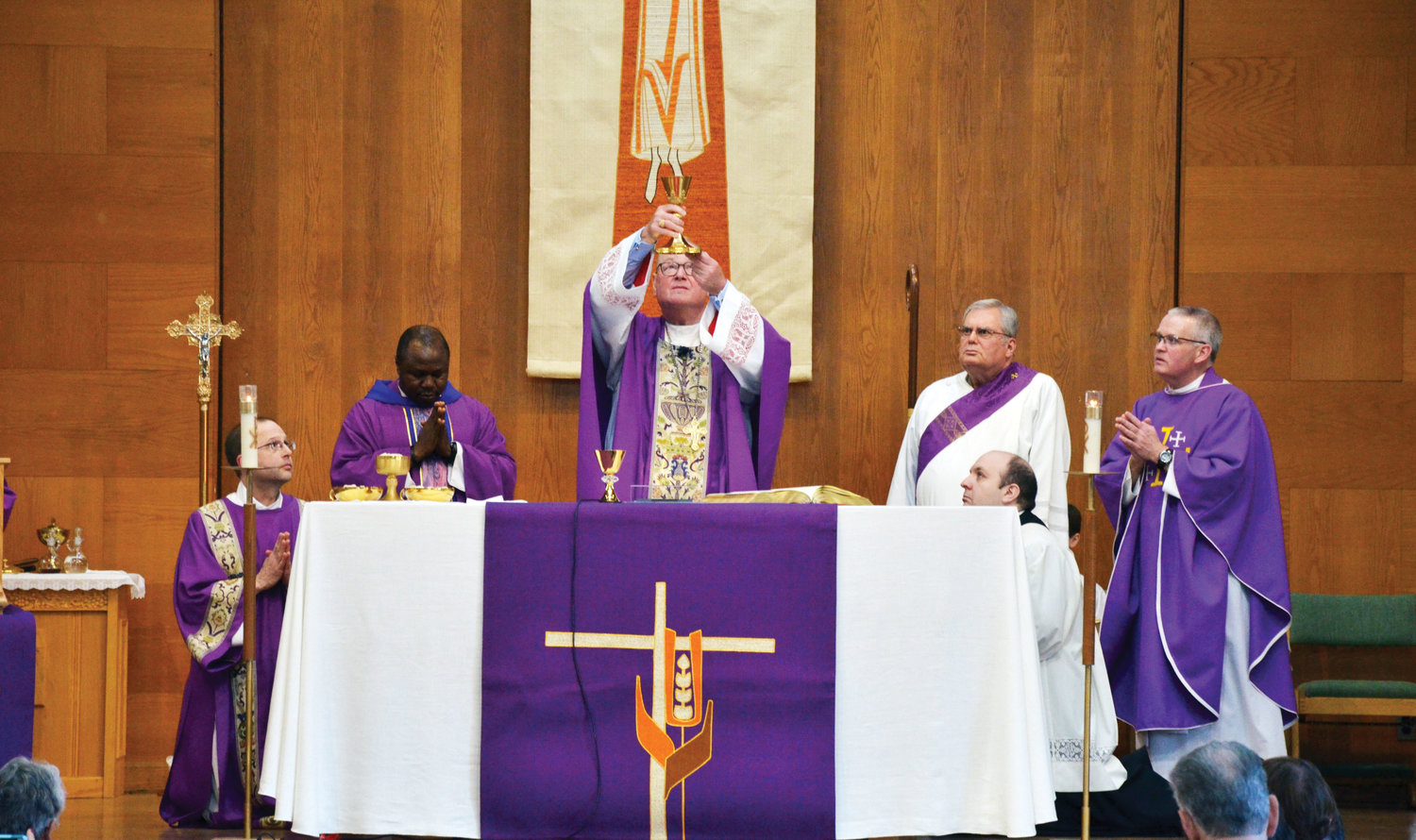 The cardinal elevates the Eucharist. From far left at the altar are Deacon Raymond Ricci, kneeling; Father David Didam, parochial vicar; Cardinal Dolan; Deacon Richard Santana; Father James Ferreira, the cardinal's priest secretary; and Father Patrick Buckley, the pastor of St. Christopher and St. Sylvia parish.