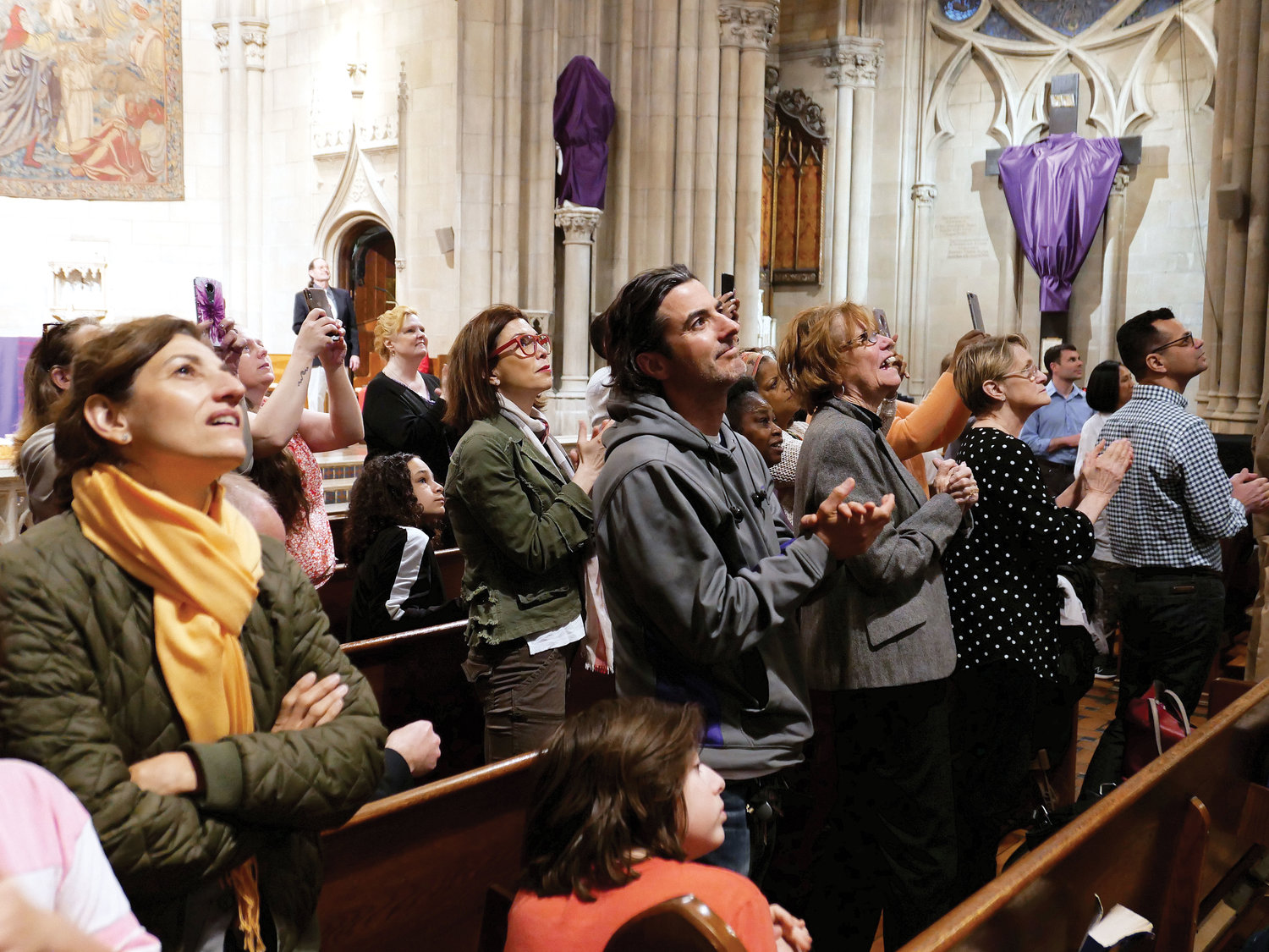 Parishioners like what they see as they gaze at the newly restored Rose Window.