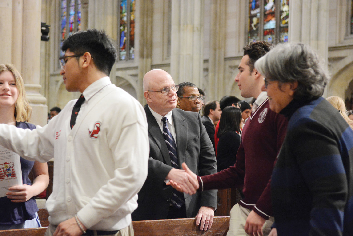 Michael Deegan, interim superintendent of schools for the archdiocese, exchanges the sign of peace with a student at a Mass for high school seniors April 4 at St. Patrick's Cathedral.