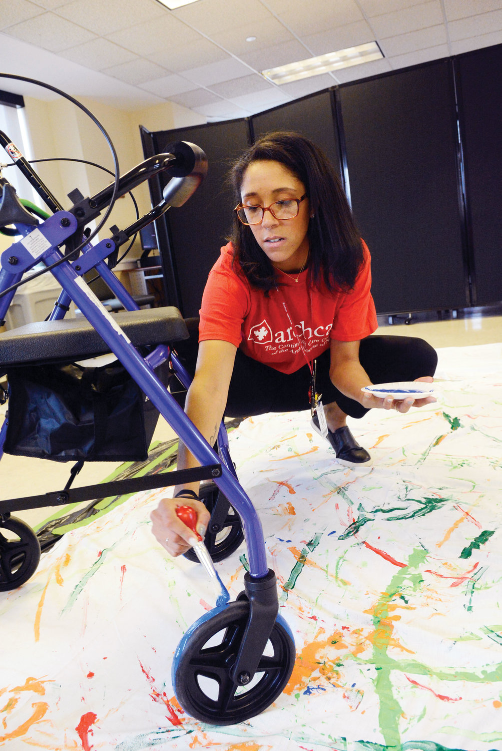 Staff, including Rebecca Love, recreational services supervisor, assisted the seniors March 25 in applying assorted colors of paint before the artists wheeled their modes of transportation across a canvas.