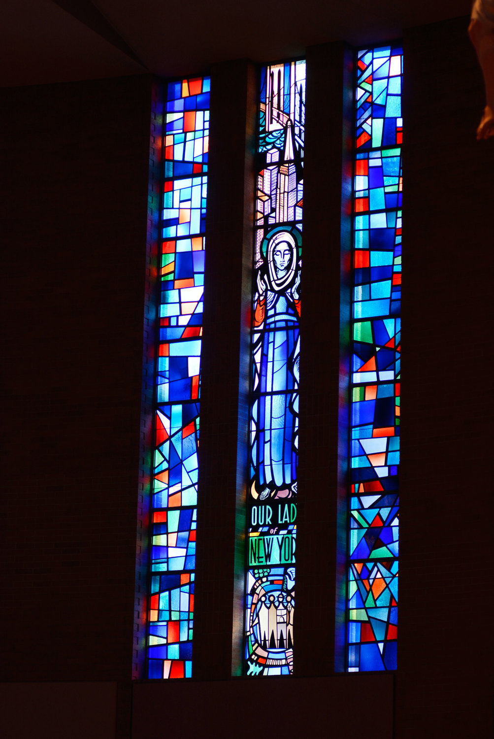 Stained glass windows in Our Lady of Perpetual Help Church capture Our Lady of New York before the Manhattan skyline.