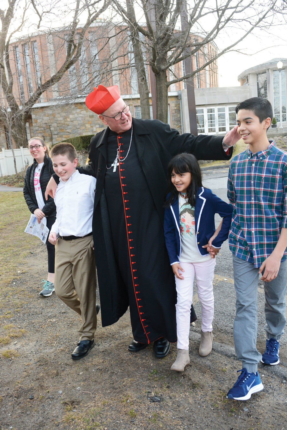 Cardinal Dolan walks with children at Our Lady of Perpetual Help and St. Catharine parish in Pelham Manor during a pastoral visit March 30.