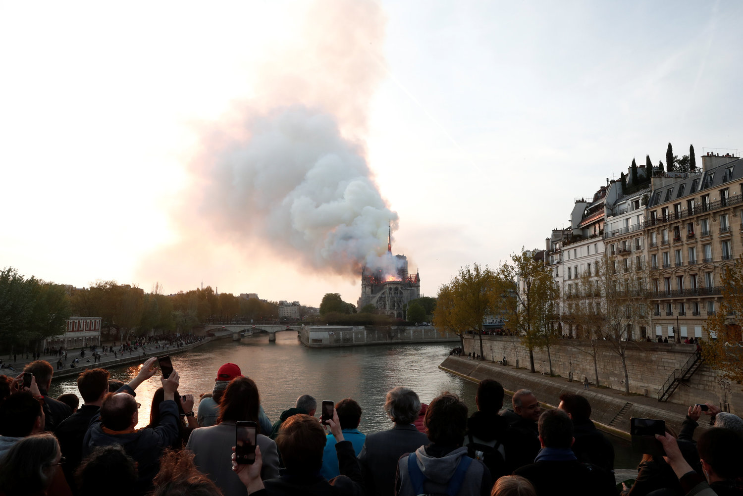 People look on as flames and smoke billow from the Notre Dame Cathedral after a fire broke out in Paris April 15.