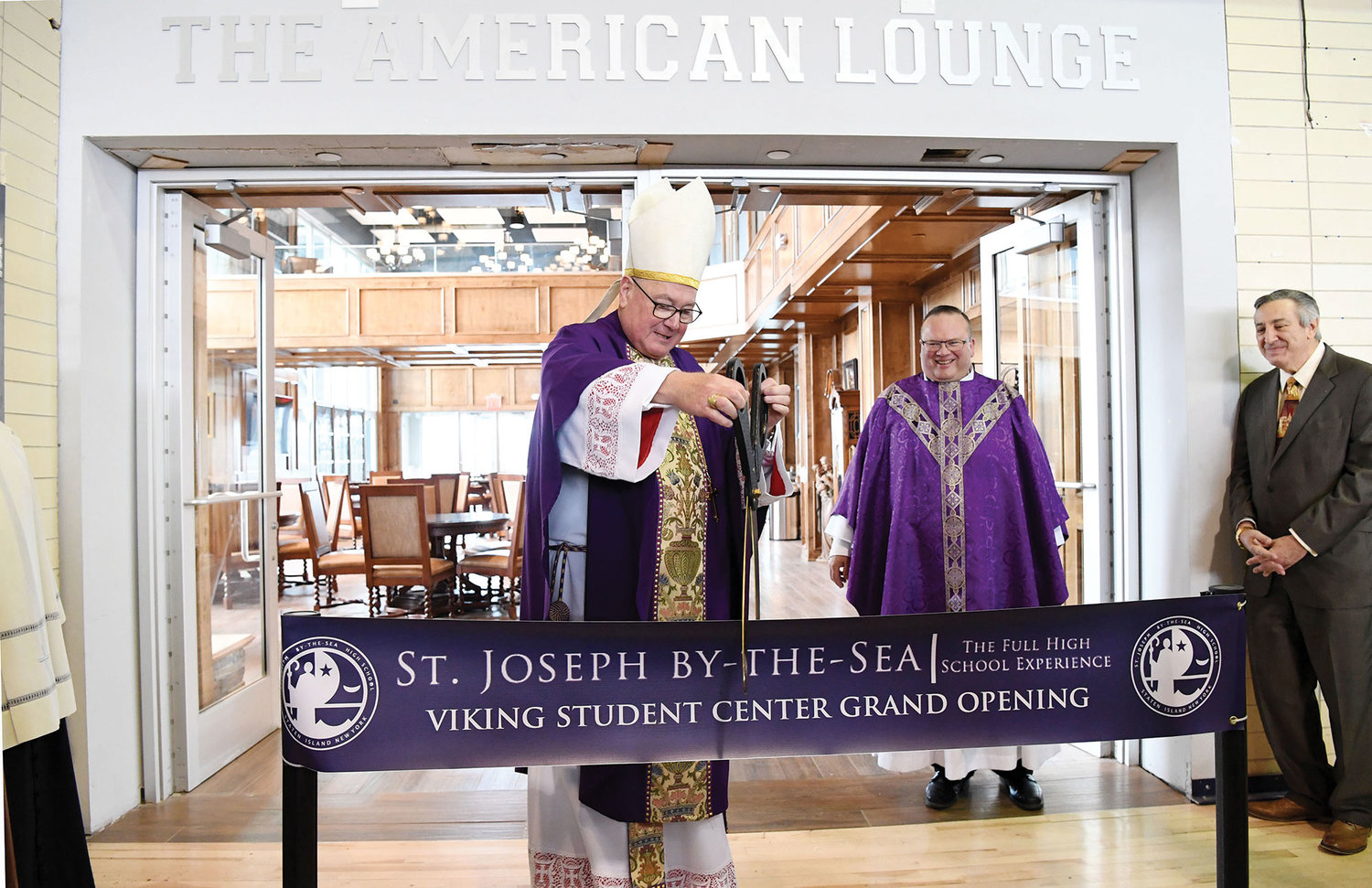 Cardinal Dolan cuts the ribbon to officially open the St. Joseph by-the-Sea High School Viking Student Center on Staten Island April 8. Looking on is Father Michael Reilly, principal.