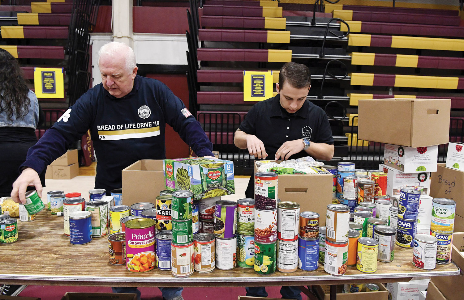 Volunteers place like food items in boxes for distribution to charities.