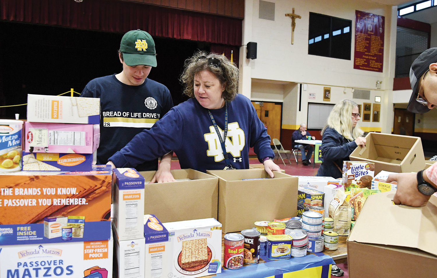 University of Notre Dame senior and Msgr. Farrell High School graduate Julio Ruiz-Gomez, left, sorts food with his mother, Elizabeth Ruiz-Gomez.