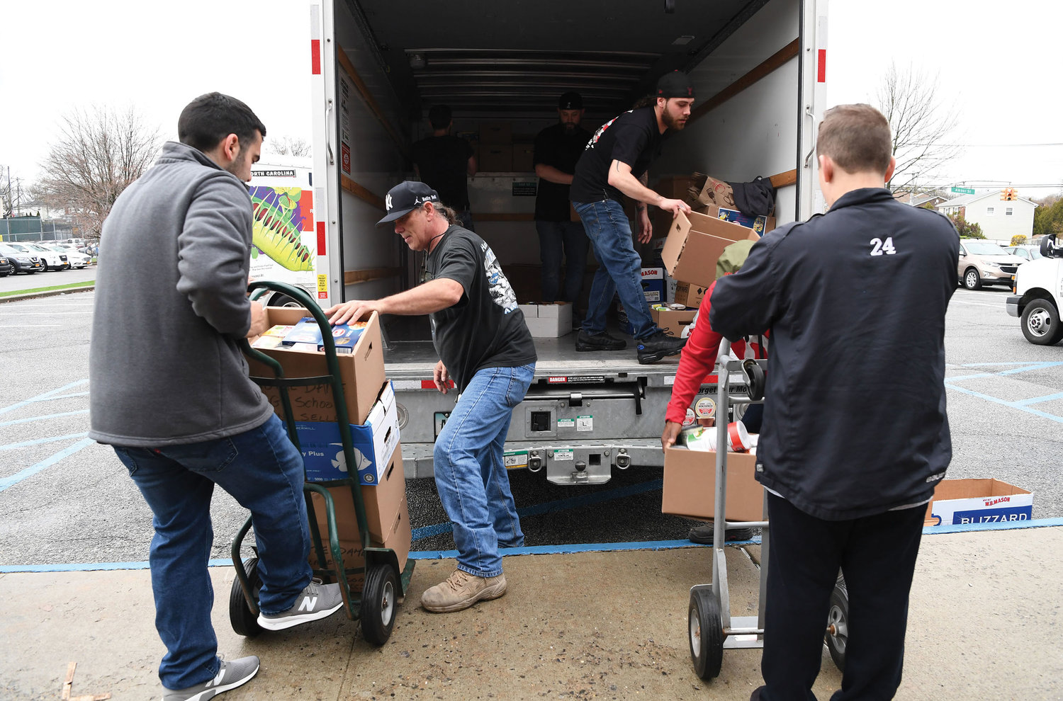 Volunteers unload a truckload of food for sorting in the gym.
