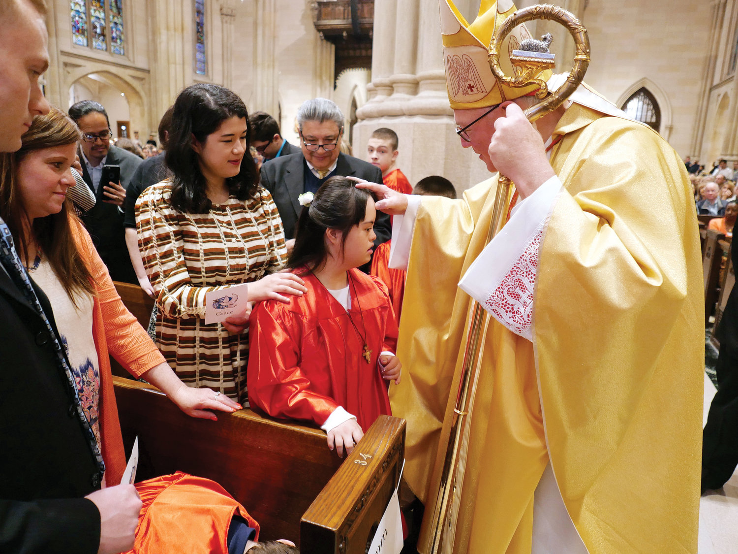 Cardinal Dolan confers the sacrament of confirmation upon Kana Welch, 17, at the Confirmation Mass for Youth with Disabilities April 28 at St. Patrick's Cathedral. Behind Kana is her sister and sponsor, Sara Welch. Kana is a member of Resurrection parish in Rye.