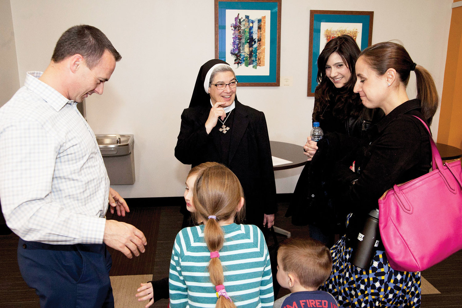 "Sister Marie Pappas, C.R., speaks with Alexandra Sullivan, hair in ponytail, and her family at Restore: Mercy in the Dominican Center at Mount St. Mary College in Newburgh April 27. Sister Marie and Ms. Sullivan had just completed their workshop, ""Femininity and Motherhood: Mercy, Truth, Beauty and Power."""