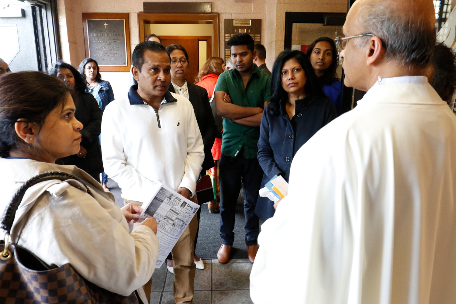 Local Sri Lankan Catholics chat with Vincentian Father John Kallattil, parochial vicar, following Mass on April 28 at St. Teresa of the Infant Jesus Church on Staten Island.