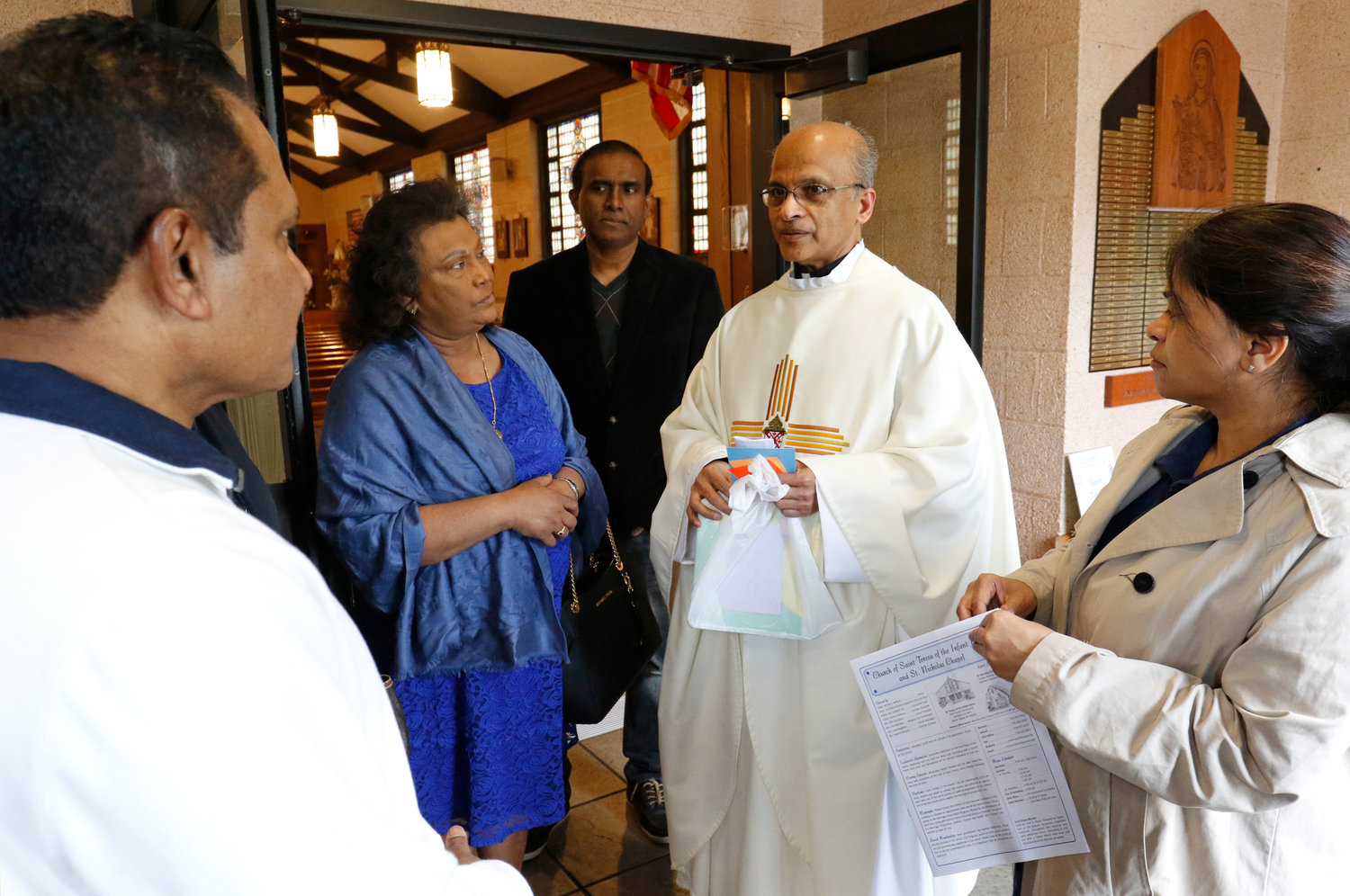Vincentian Father John Kallattil, parochial vicar, chats with local Sri Lankan Catholics following Mass on April 28 at St. Teresa of the Infant Jesus Church on Staten Island.