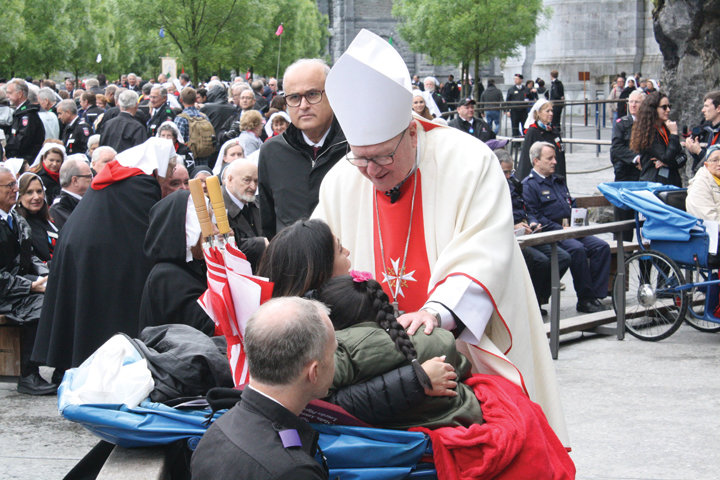 LOURDES ENCOUNTER—Cardinal Dolan greets a young malade and her mother following a Mass May 4 at the Grotto in Lourdes, France, for pilgrims with the Order of Malta's three U.S. associations, American, Federal and Western.