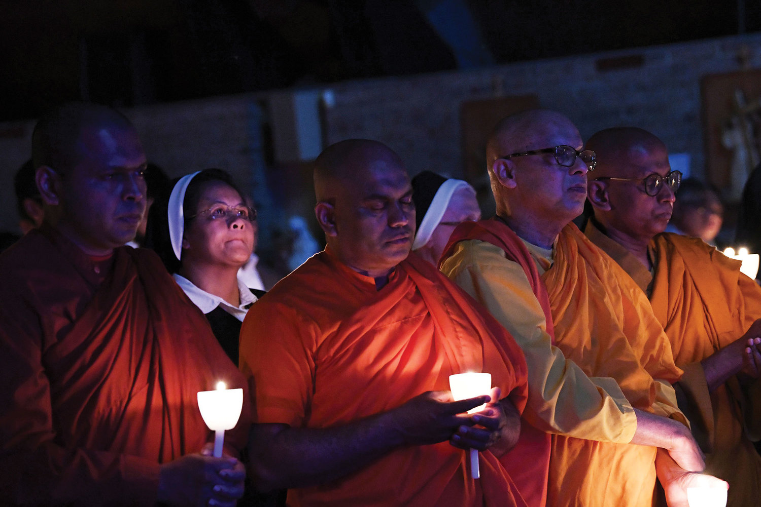 Religious sisters and Buddhist monks participate in a candlelight prayer ceremony at the end of the Mass offered May 12 at St. Adalbert Church on Staten Island in memory of the victims of the Easter Sunday bombings in Sri Lanka.