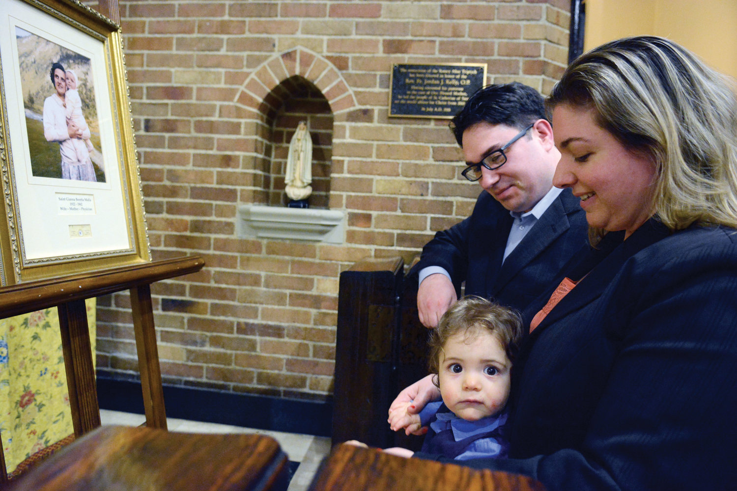 Jason and Carrie Caminiti kneel with their 14-month-old son Christian during veneration in front of a framed photo and relic of St. Gianna Beretta Molla at St. Catherine of Siena Church in Manhattan May 16.