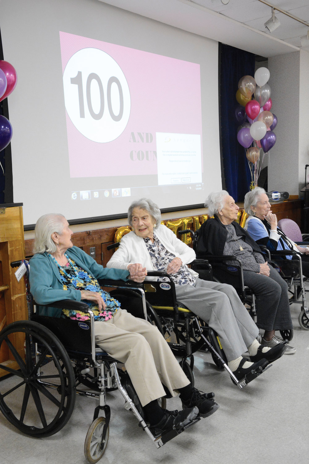 Sisters Pauline Carbone, 104 years old, and Anne Gordon, 100, hold hands as ArchCare at Mary Manning Walsh Home in Manhattan May 14 celebrated the lives of 11 residents aged 100 to 106, and two more turning 100 in the coming months.