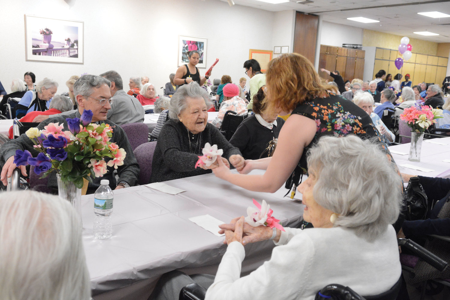 Josephine Pulick, 104, dances from her seat with recreation therapist Caitlin Kelly.
