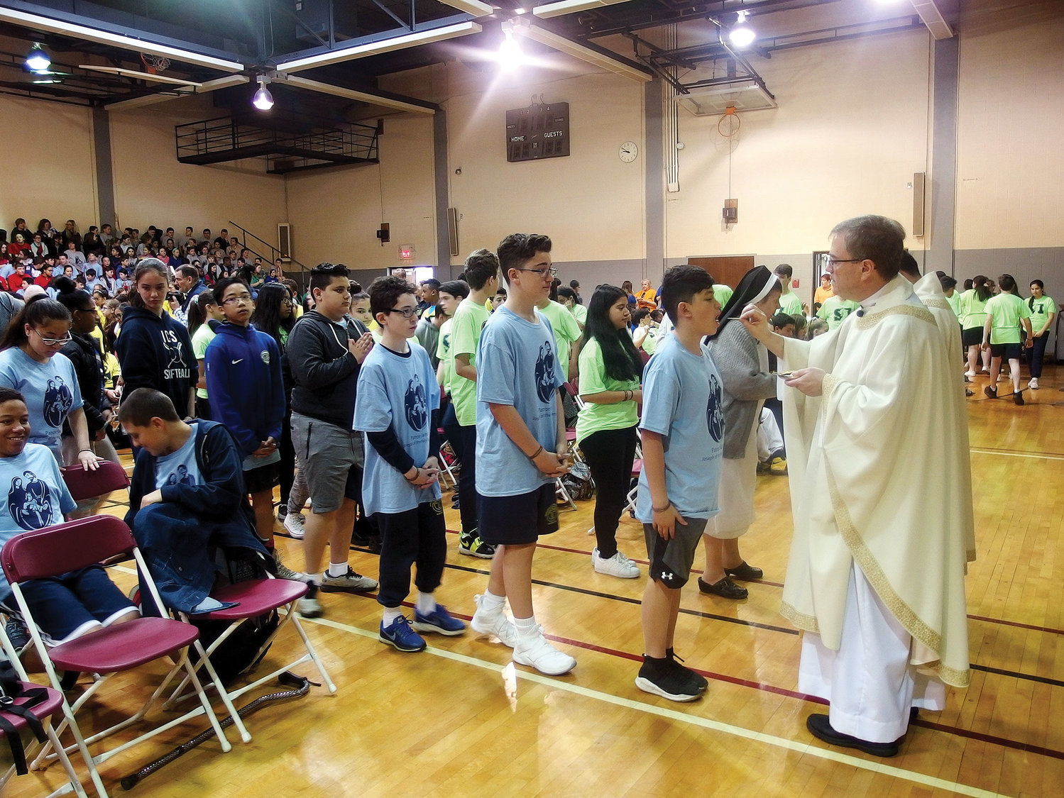 Father Michael McLoughlin, pastor of St. Columba parish, Hopewell Junction, and celebrant of the field day liturgy, distributes Holy Communion in the seminary gym.