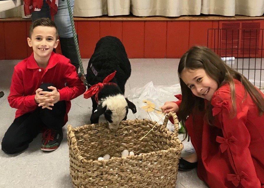 Siblings Dominick and Valentina Misiano enjoy their time with Bonnie the lamb in the church hall at Sacred Heart parish in Patterson on Good Shepherd Sunday, May 12.