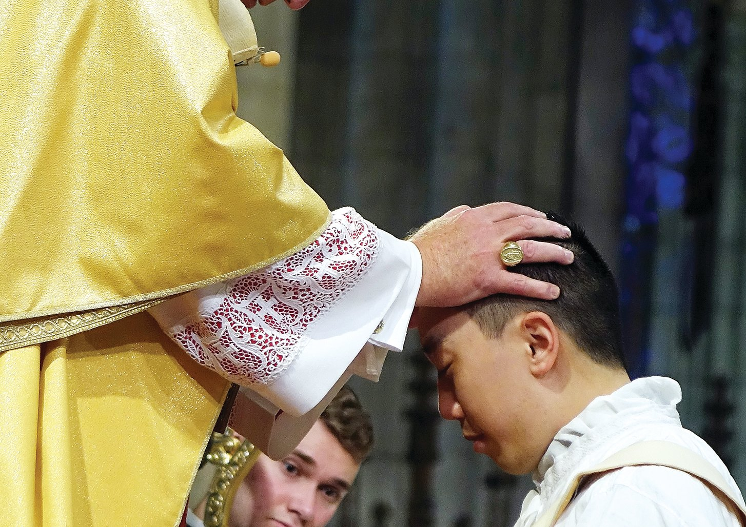 Cardinal Dolan lays hands on the head of Father Roger Kwan.